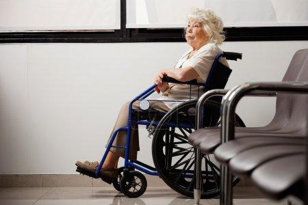 Photo pour Femme âgée songeuse sur fauteuil roulant en attente dans le hall de l'hôpital - image libre de droit