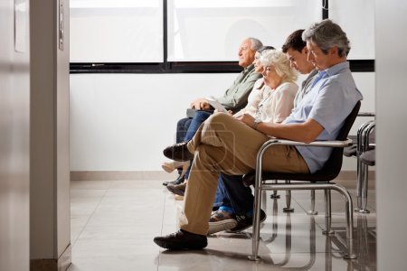 Photo for Row of multiethnic sitting side by side while waiting for doctor in hospital lobby - Royalty Free Image