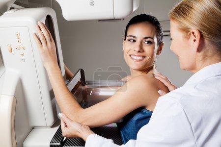 Photo pour Heureuse patiente regardant un médecin pendant un test de mammographie - image libre de droit
