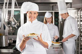 Happy Chef Presenting Dish In Industrial Kitchen