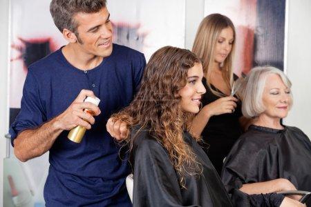 Photo pour Coiffeurs masculins et féminins installant les cheveux du client dans le salon - image libre de droit