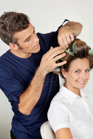 Customer With Hairstylist Curling Hair At Parlor