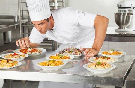 Photo pour Jeune chef masculin garnissant des plats au comptoir de cuisine commerciale - image libre de droit
