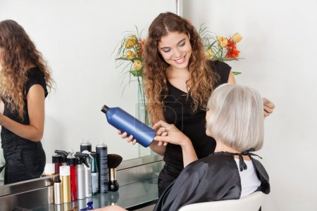 Hairstylist Advising Hair Color To Senior Client