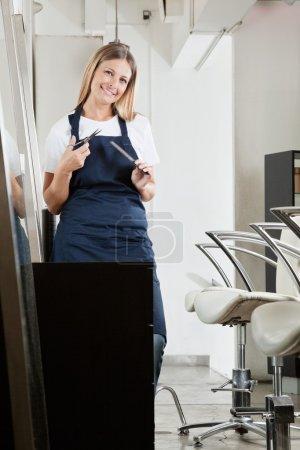 Photo pour Portrait de coiffeuse avec peigne et ciseaux au salon - image libre de droit