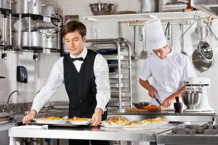 Photo for Young waiter carrying tray of dishes with chef working in commercial kitchen - Royalty Free Image