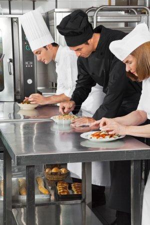 Photo pour Chefs garnissant des plats de pâtes sur le comptoir de la cuisine du restaurant - image libre de droit