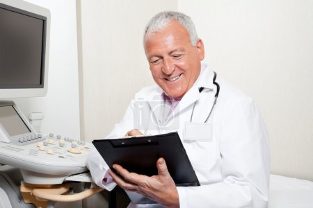 Photo for Happy senior male radiologist holding clipboard while sitting in clinic - Royalty Free Image