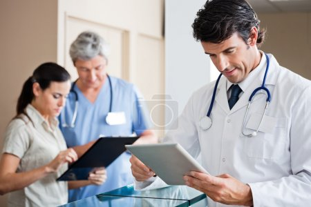 Mid adult male doctor holding digital tablet with colleague and receptionist standing in background