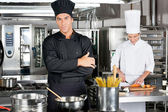 Confident Chef With Colleague In Kitchen