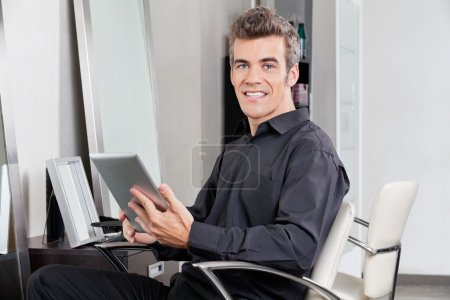 Male Customer With Digital Tablet Sitting At Salon