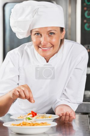 Photo for Portrait of happy female chef adding spices to food at commercial kitchen counter - Royalty Free Image