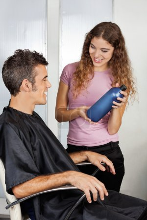 Hairdresser Presenting Shampoo Bottle To The Client