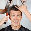 Hairdressers hands setting up male client's hair a...
