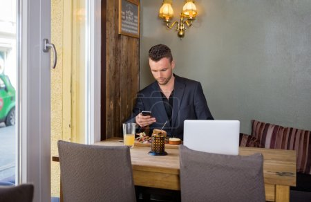 Business man Messaging On Cellphone While Having Food
