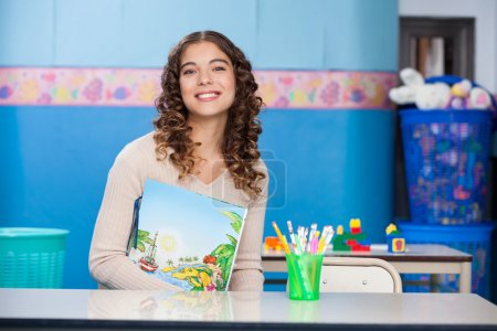 Teacher With Book Sitting At Desk In Kindergarten