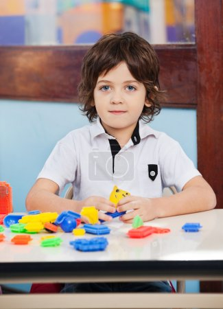 Little Boy With Construction Blocks Playing In Class