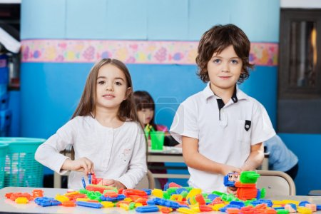Cute Friends Playing With Blocks At Desk In Kindergarten