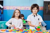 mignons amis à jouer avec des blocs au comptoir à la maternelle