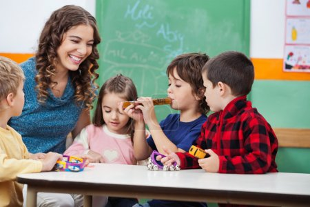 Photo for Happy teacher with children playing musical instruments in classroom - Royalty Free Image