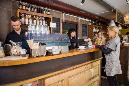 Photo pour Jeune femme barman servant du café au client avec un collègue masculin travaillant au comptoir - image libre de droit