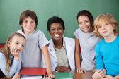 Cute Schoolchildren With Female Teacher At Desk