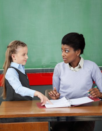 Schoolgirl Pointing In Binder While Teacher Looking At Her