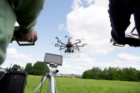 Photo for Octocopter being operated by a photographer and pilot in open green park - Royalty Free Image