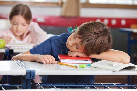 Foto de Escuela primaria niño durmiendo mientras chica estudia en segundo plano en el aula - Imagen libre de derechos