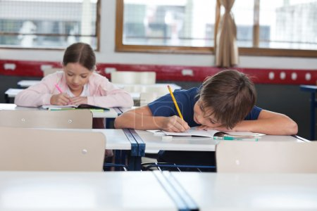 Boy And Girl Studying In Classroom