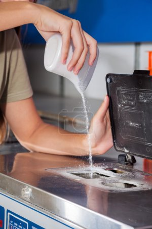 Photo for Cropped image of woman pouring detergent powder in washing machine in laundromat - Royalty Free Image