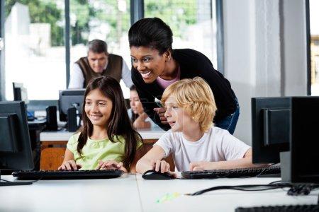 Happy Teacher Assisting Schoolchildren In Using Computer