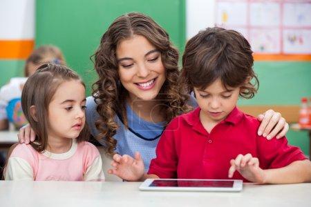 Photo pour Enfants à l'aide de tablette numérique avec professeur au comptoir de la salle de classe - image libre de droit