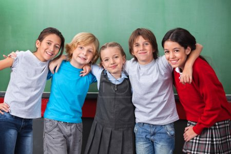 Photo pour Portrait de petits écoliers mignons avec les bras autour debout contre tableau dans la salle de classe - image libre de droit