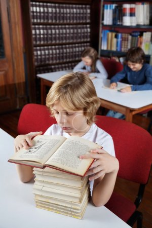 Schoolboy With Stacked Books Reading In Library