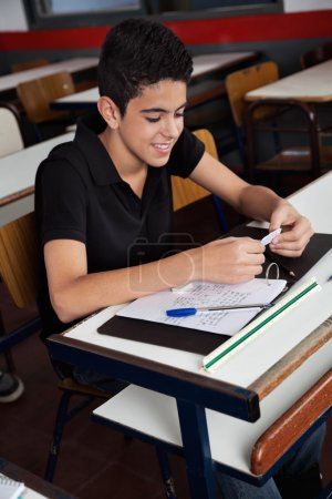 Schoolboy Copying From Cheat Sheet At Desk