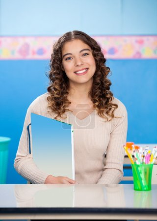 Teacher Holding Book While Sitting At Desk