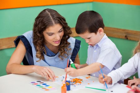Boy Painting While Teacher Assisting Him