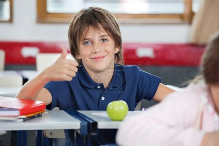Boy Gesturing Thumbs Up In Classroom
