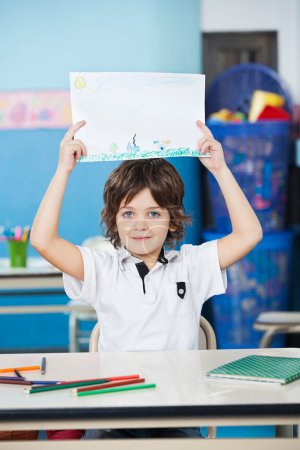 Boy Holding Drawing Paper At Desk In Kindergarten