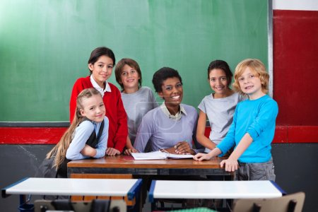 Happy Teacher And Schoolchildren Together At Desk In Classroom