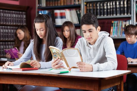 Photo for Male and female friends studying at table with classmates in library - Royalty Free Image