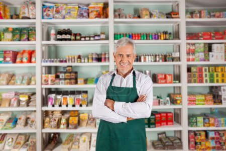 Photo for Portrait of happy senior male owner standing arms crossed against shelves in supermarket - Royalty Free Image