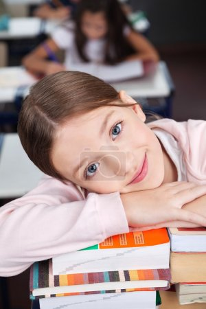 Photo for Portrait of cute little schoolgirl leaning on stack of books in classroom - Royalty Free Image