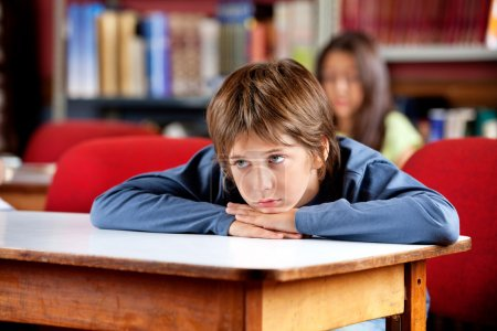 Bored Schoolboy Looking Away While Leaning On Table