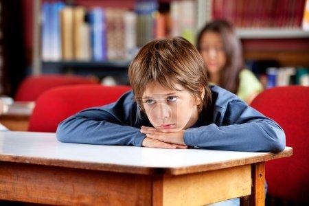 Foto de Colegial poco aburrido apartar la mirada mientras apoyado en la mesa en la biblioteca con una compañera de clase en segundo plano - Imagen libre de derechos