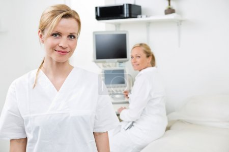 Happy Female Gynecologist With Colleague In Background