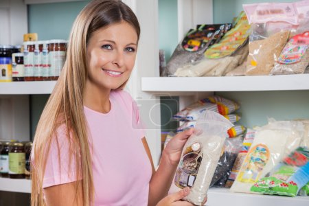 Photo for Portrait of beautiful mid adult woman holding food packet in grocery store - Royalty Free Image