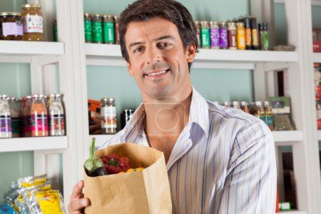 Photo for Portrait of handsome male customer with vegetable bag standing against shelves in supermarket - Royalty Free Image