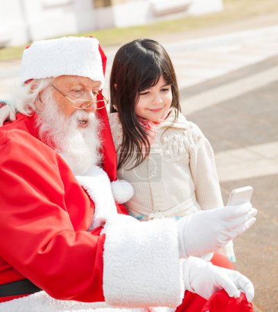 Girl And Santa Claus Taking Selfportrait Through Smartphone